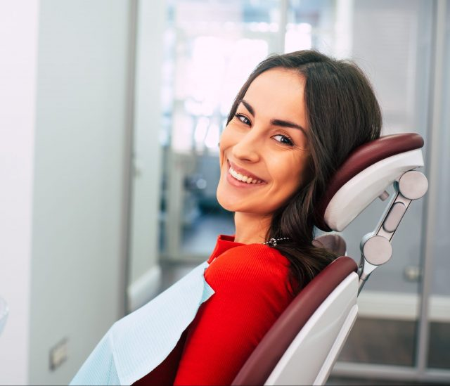 New Life With New Teeth. Gorgeous Girl Wearing Red Sweater In The Stomatology Room Full Of Day Light And White Colors Is Smiling With Her New White Eye Catching Smile.